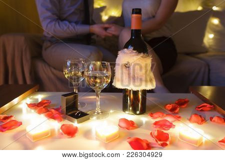 couple In Love On Sofa Celebrating Engagement At Home At Night. Focus On The Table With Glasses Of