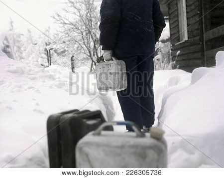Man In Focus Walking With Jerry Can, A Bunch Of Petrol Cans In The Foreground