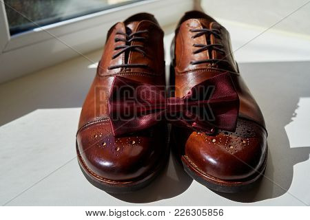 Close Up Of Burgundy Man Bowtie On Brown Leather Man Shoes. Modern Man Accessories. Wedding Details.