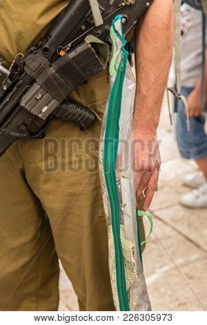 A soldier in uniform and with a gun holds a cover for the lulav. Sale of ritual plants on the traditional market in the Jerusalem. Ancient Jewish holiday Sukkot