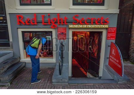 Amsterdam, The Netherlands - June 10, 2014: Young Tourists Standing At Entrance To Prostitution Muse