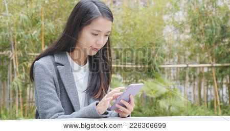 Businesswoman work on cellphone in the park