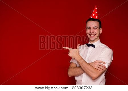 Happy Man A White Shirt A Red Cap Pointing Finger And Looking In Camera. Photo For Business Projects