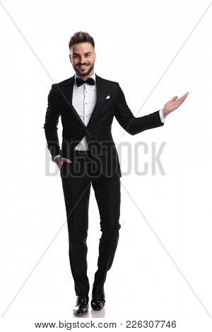 happy young elegant man presenting or welcoming on white background