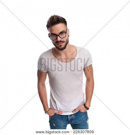 young happy smart hipster standing with hands in pockets smiling to the camera on white background