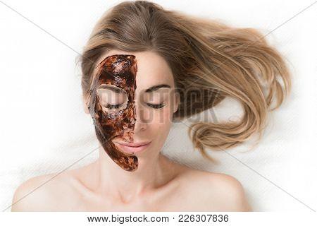 Facial Mask. Beautiful young woman relaxing in beauty spa salon, applying chocolate face mask