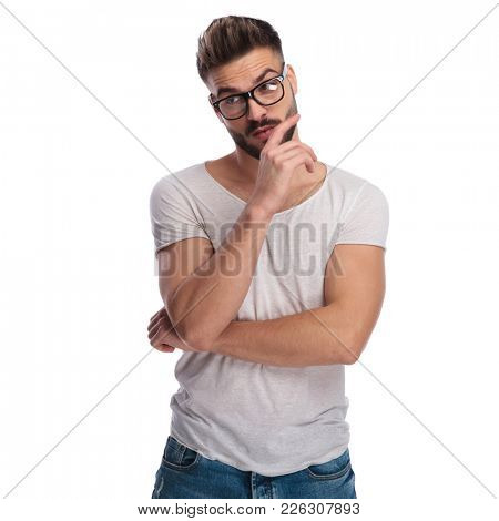 pensive casual man making a stupid face and looks to side on white background