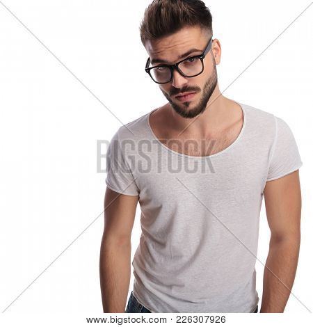 young casual man wearing glasses is standing on white background