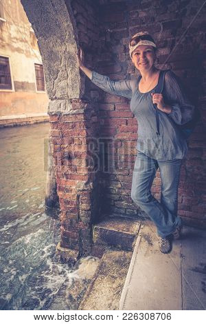 Girl Tourist Stands At The Water's Edge At The Door In Venice