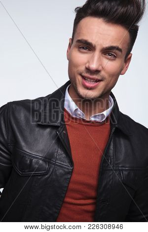 headshot picture of a cool young fashion guy smiling on grey background