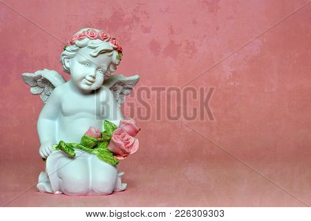 Cute Little Angel Kneeling And Holding Flowers