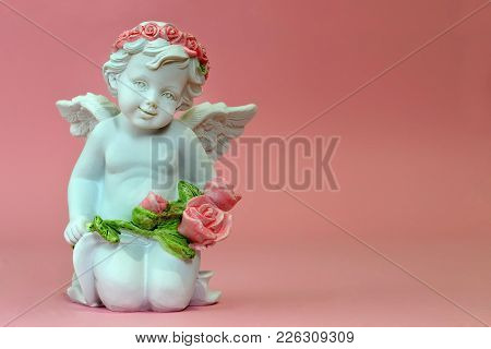 Little Guardian Angel Kneeling And Holding Pink Flowers