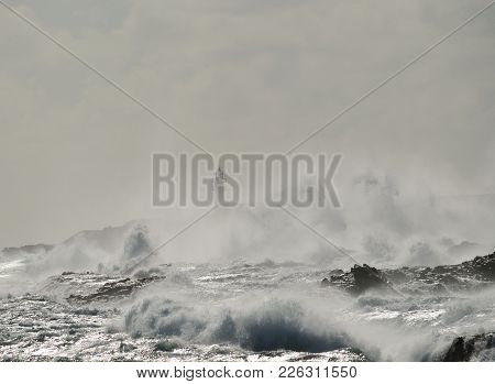 Strong Swell On The Coast And Blurred Silhouette Of Lighthouse In Background, Telde, Canary Islands