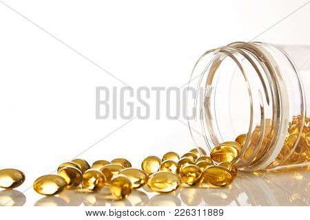 Cod Liver Oil Omega 3 Gel Capsules. Fish Oil Vitamines Spilling Out Of Prescription Bottle Over Whit