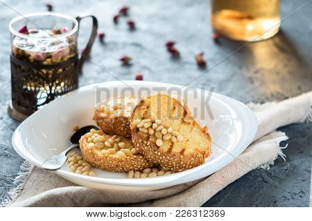 Toasts Of Bread With Sesame Seeds Homemade Cake In Stack Decorated With Pine Nut On White Plate With