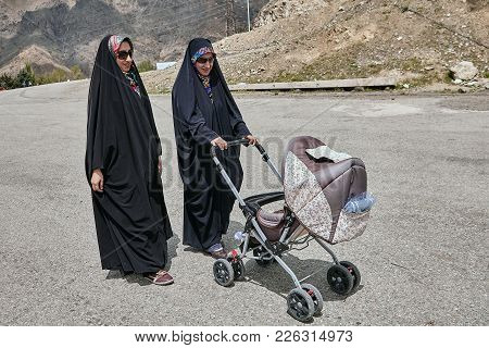 Tehran, Iran - April 28, 2017: Two Iranian Women In Religious Veil Are Walking Along The Street With