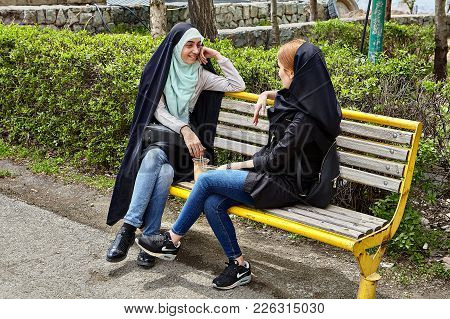 Tehran, Iran - April 28, 2017: Two Iranian Women In Hijabs Sit On A Bench In The Park And Talk.
