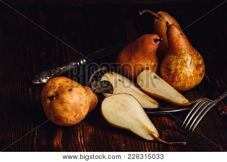 Few Golden Pears On Wooden Table With Sliced One, Fork And Knife.