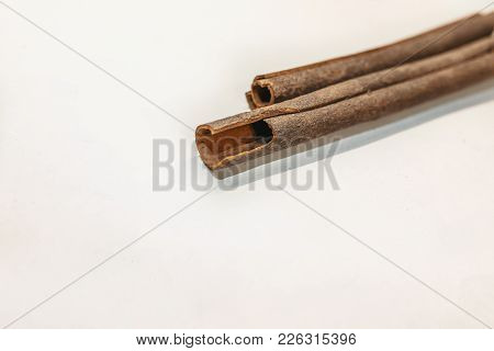 Top View Of Cinnamon Sticks Isolated On White. Three Cinnamon Sticks In The Recipes Of Cosmetics And