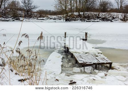 Footbridge In A Partly Frozen River In Cloudy Winter Day With An Ice Bricks Laying On Top Of It