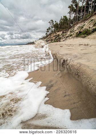 Tidal sea waves hitting beach bank - Ustka beach, Poland