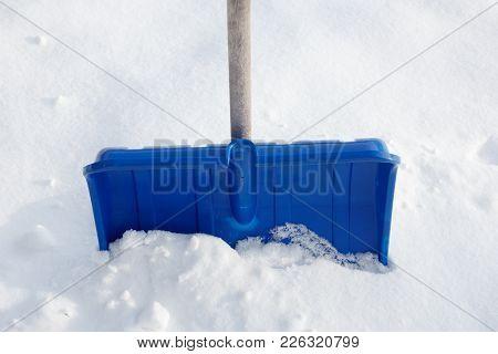 Blue Snow Shovel In Freshly Snowy Snow