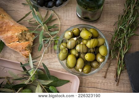 bread ciabatta and bowl of green olives background
