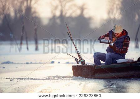 Winter season- senior man on frozen lake and drink hot tea