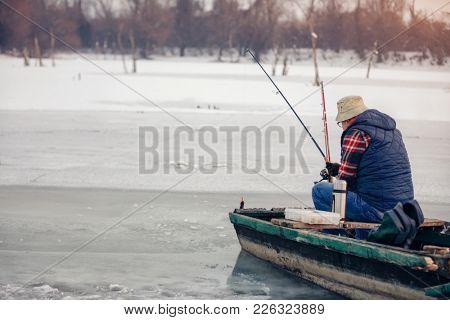 Winter season old man fishing on frozen lake