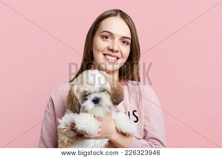 Positve Female With Long Hair And Pleased Expression Holds Her Favourite Little Puppy, Isolated Over