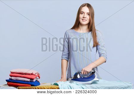 Isolated Shot Of Hard Working Female Busy With House Work, Stands In Laundry, Irons Clothes With Ele