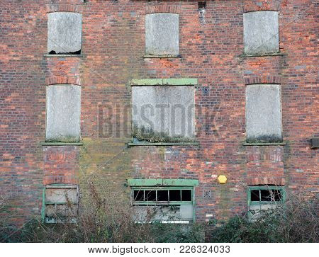 Facade Of A Derelict Abandoned Old Brick Industrial Building With Broken Boarded Up Decaying Windows