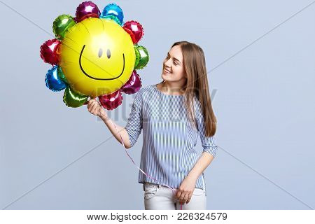 Positive Female Celebrates Her Birthday, Holds Balloon In Form Of Sun, Has Festive Mood, Dressed In