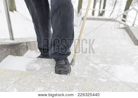 An Elderly Retired Man With A Wand Climbs The Marble Staircase In The Park. Holds On The Railing. St