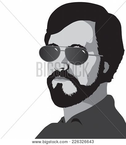 A Bearded Man Wearing Sun Glasses Is Looking Toward Viewer