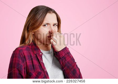 Sideways Portrait Of Displeased Young Female Covers Nose As Smells Stink, Has Discontent Expression,