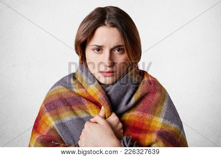 Horizontal Shot Of Pretty Young Woman Feels Cold, Wrapped In Wool Coverlet, Tries To Warm Herself, I