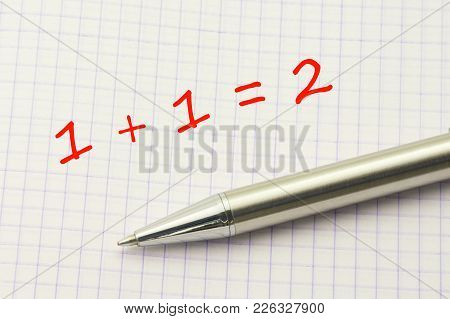 1 Plus 1. Simple Equation On A Squared Paper Sheet With A Silver Pen. It Is Simple To Study. Mathema