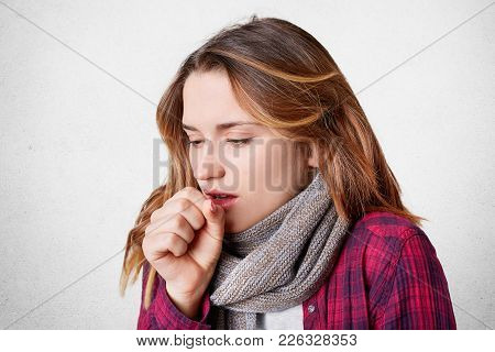 Unhappy Female Coughs As Caught Cold On Frosty Weather, Wears Warm Scarf On Neck, Has Thore Throat,