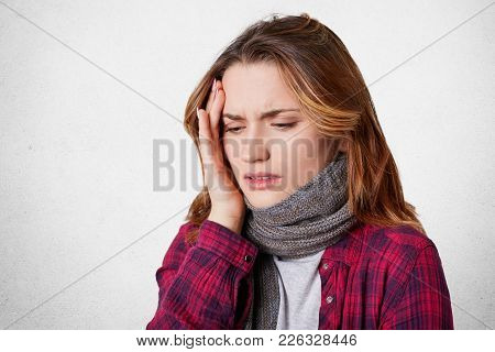 Unhealthy Ill Woman Feels Terrible Headache, Keeps Hand On Head, Wears Warm Knitted Scarf And Casual