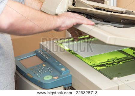 Young Man Using A Copy Machine To Replicate Documents Or To Make Digital Scans