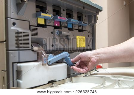 Hand Of A Man Replacing Ink Cartridge On A Professional Printing Machine