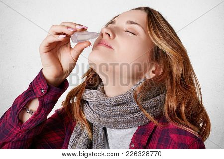 Adorable Young Woman Has Blocked Nose, Dripps Nasal Drops, Isolated Over White Background. Young Fem