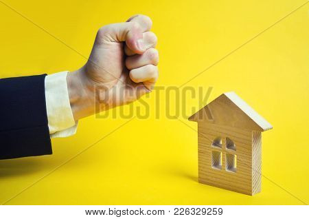 Concept Of Threat To Home And Real Estate, Business Threat. The Hand Of The Fist Tries To Hit The Ho