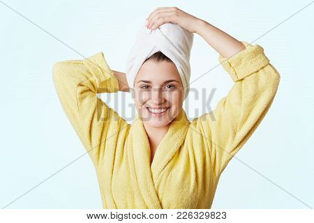 Glad Beautiful Female Wears Bathrobe And Towel On Head, Glad To Take Shower, Has Appealing Appearanc