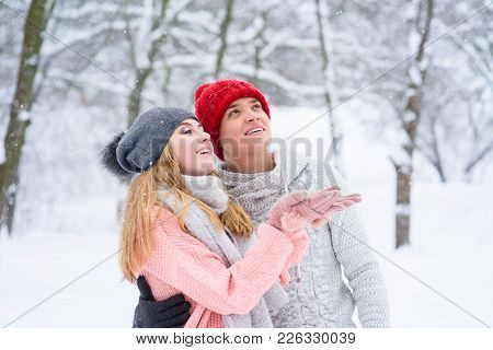 Girl And Boy Teenagers In Knitted Hats And Sweaters During Snowfall
