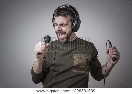 Young Man Singing Karaoke And Dancing, Moving His Body In The Rhythm Of The Music