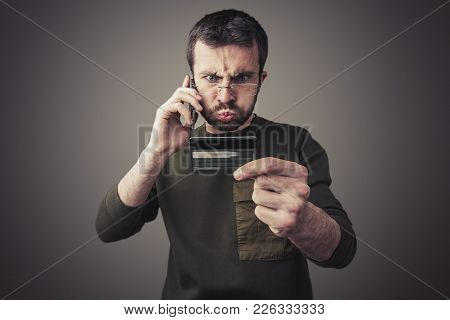 Angry Young Man Having An Argument With His Bank For The Credit Card Bill He Received