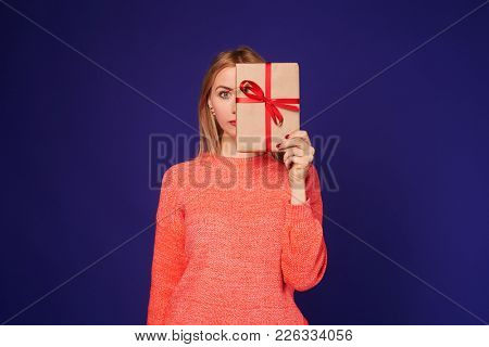 blond hiding face behind gift box