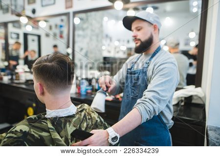A Stylish Barber With A Beard Finishes A Male Hairstyle To The Client. Men's Haircuts In Barbershop.